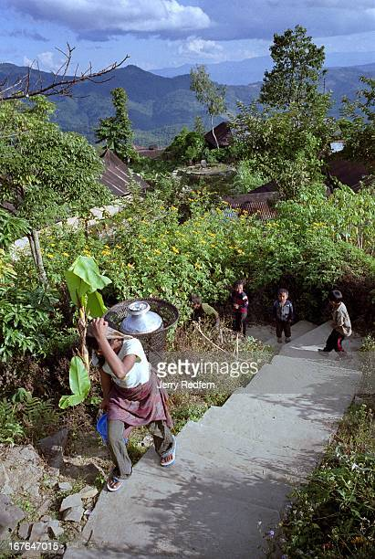A young woman carries a tin of water up a steep staircase through a traditional Naga village Such villages are historically built atop hills the...