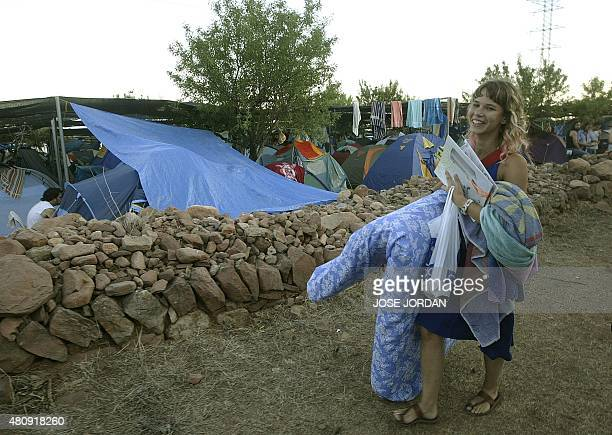 A young woman carries her bedding in one of the three campings at the Benicassim Festival Benicassim 05 August 2005 AFP PHOTO/ JOSE JORDAN