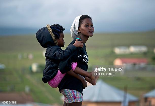 A young woman carrying a baby looks towards Nelson Mandela's family house in Qunu where the coffin of South African former president arrived on...