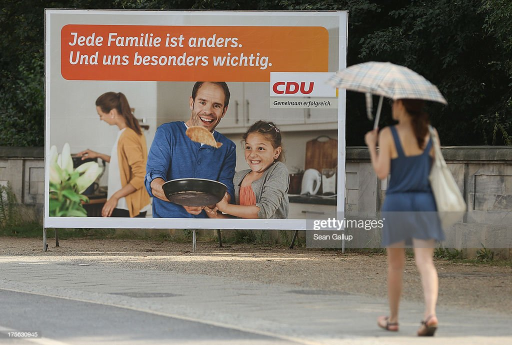 A young woman carrying an umbrella against the sun walks past an election campaign poster of the German Christian Democrats (CDU) that reads: 'Every family is different. And especially important to us.' on August 6, 2013 in Berlin, Germany. Germany is scheduled to hold federal elections on September 22 and so far current Chancellor Angela Merkel and her party, the German Christian Democrats (CDU), have a strong lead over the opposition.