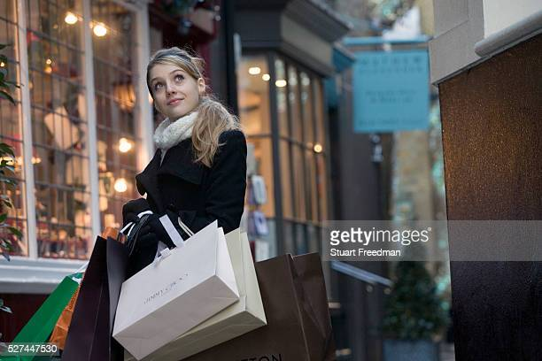 A young woman carrying bags from designer shops shopping in the affluent Mayfair area of London