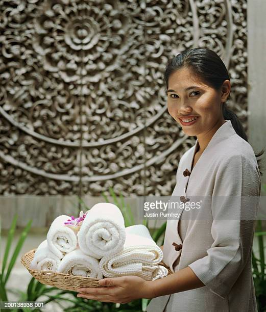 Young woman carrying basket of neatly rolled towels, smiling, portrait