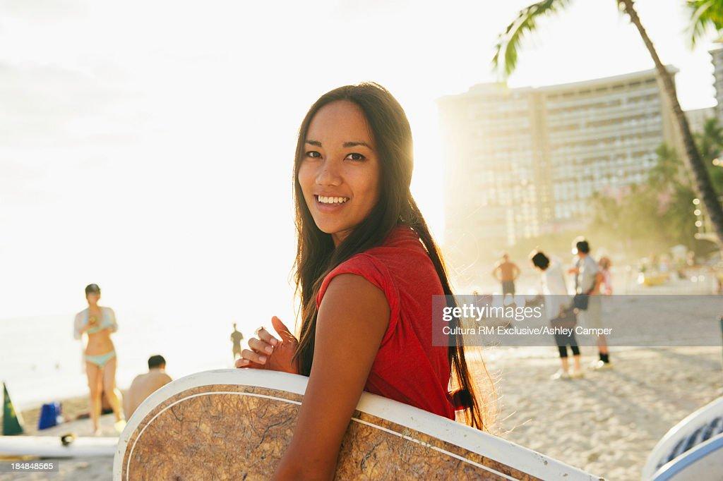 Young woman carrying bodyboard, Honolulu, Hawaii : Stock Photo