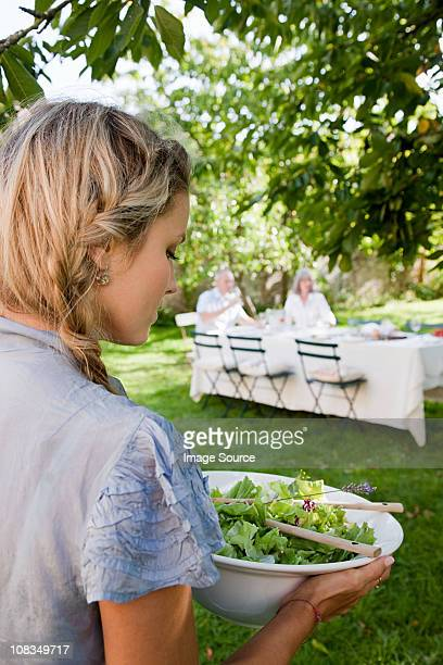 Young woman carrying bowl of salad