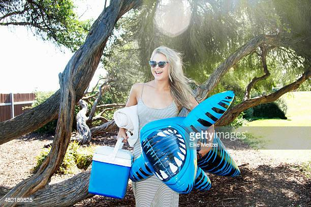 Young woman carrying cool box and inflatable tiger shark, Melbourne, Victoria, Australia