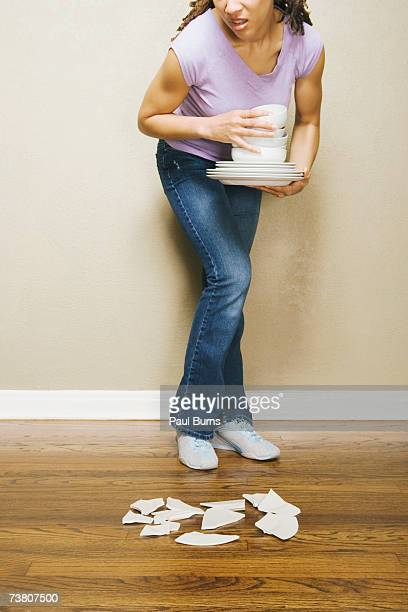Young woman carrying crockery looking at dish dropped on floor, cropped
