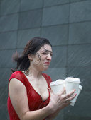 Young woman carrying disposable cups in rain, eyes closed