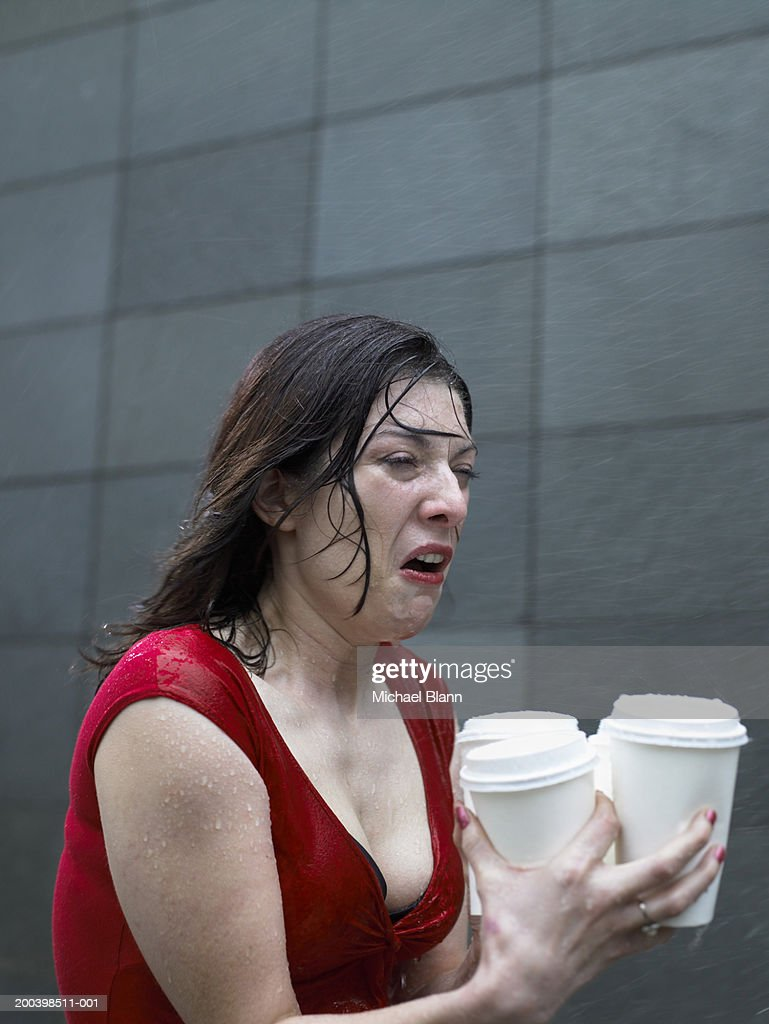 Young woman carrying disposable cups in rain, pulling face