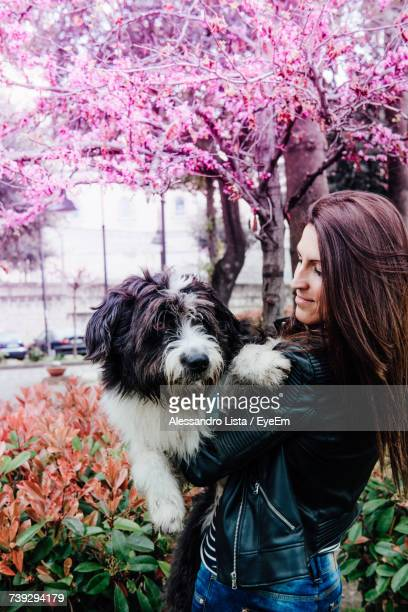 Young Woman Carrying Dog By Pink Flowering Tree