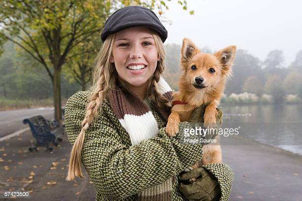 Young woman carrying dog in the park