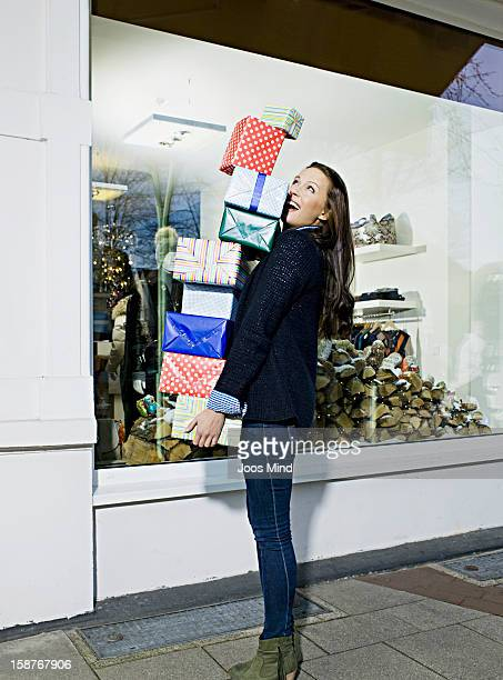 young woman carrying gift packs infront of shop