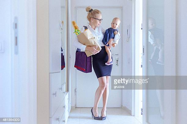 Young woman carrying grocery and a baby girl, coming home