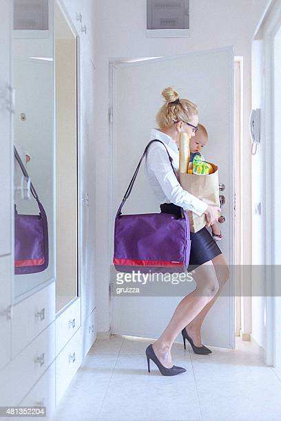 Young woman carrying grocery and her baby closes the door
