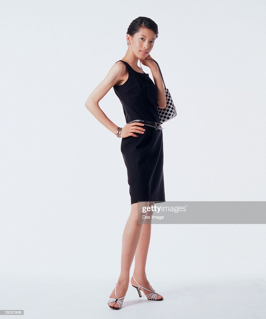 Young woman carrying handbag, hand on hip : Stock Photo