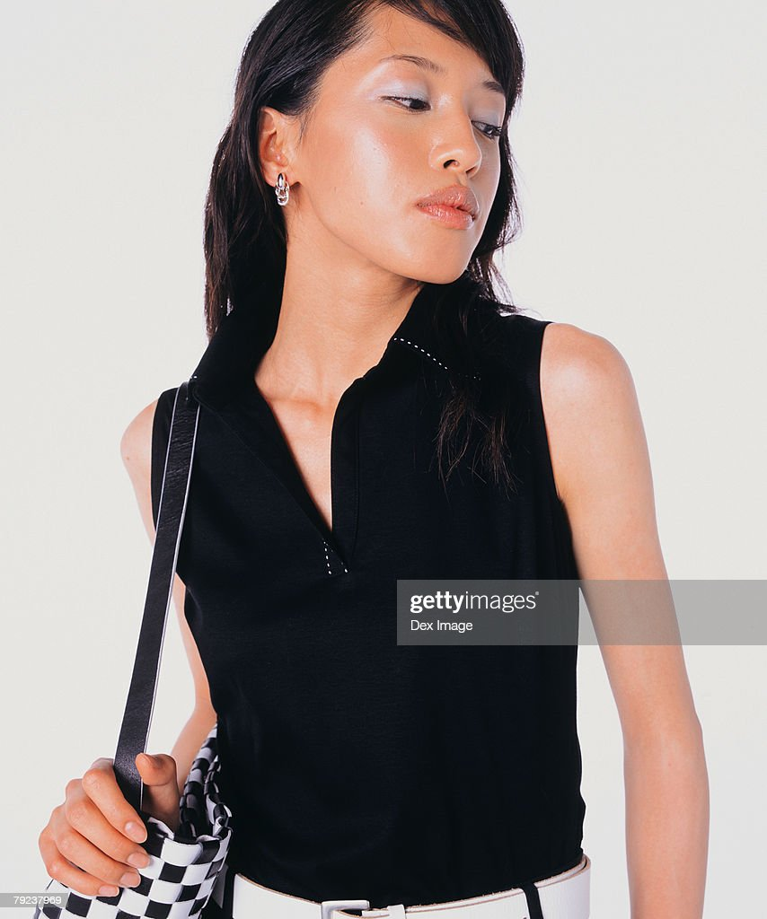 Young woman carrying handbag, posing : Stock Photo