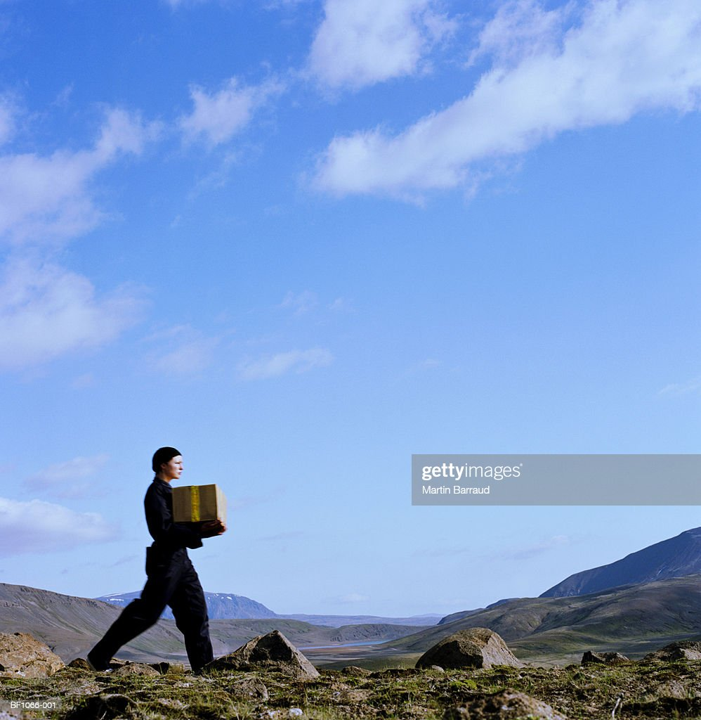 Young woman carrying parcel across rocky terrain, profile : Stock Photo