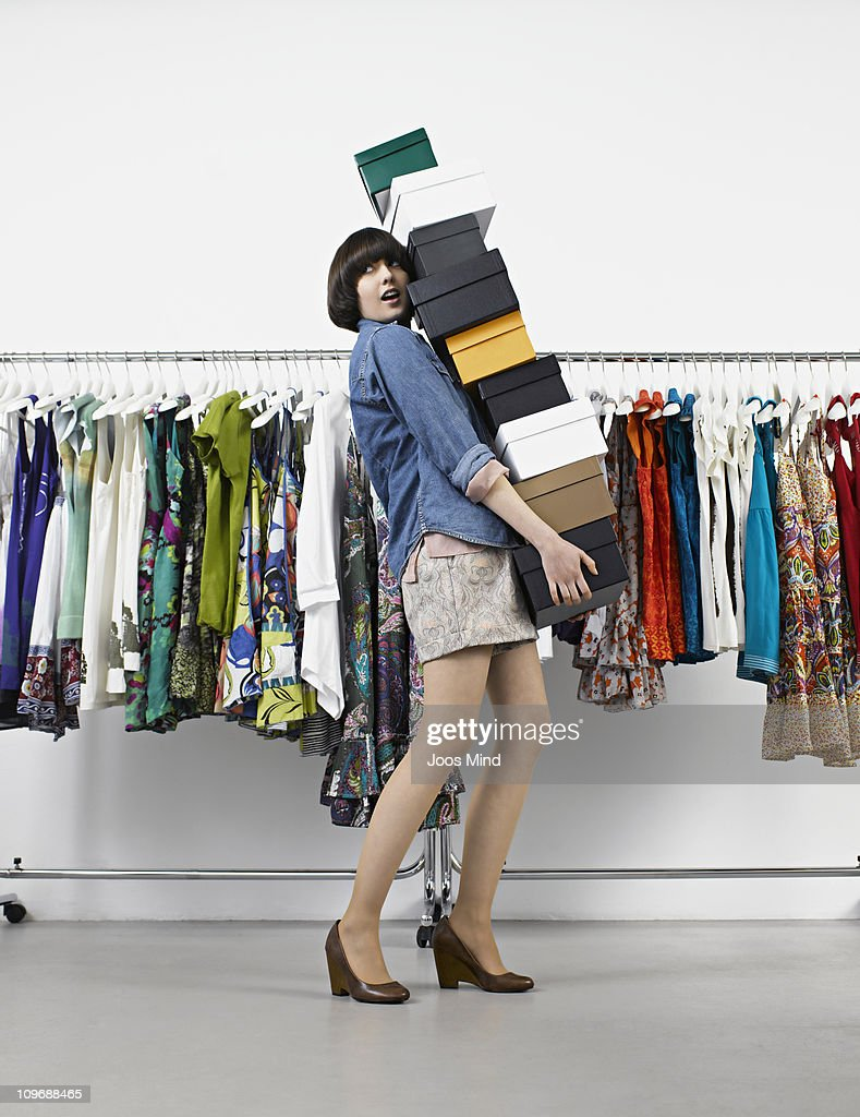 young woman carrying shoe boxes in store : Stock Photo