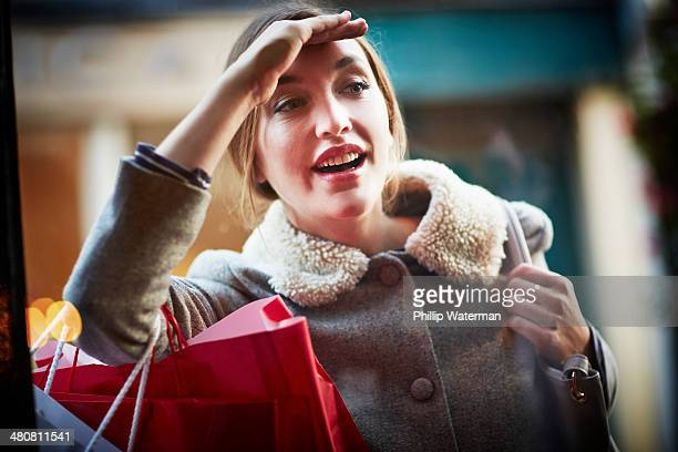 Young woman carrying shopping bag, looking through window