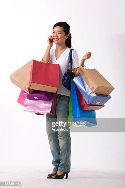 Young woman carrying shopping bags and talking on a mobile phone