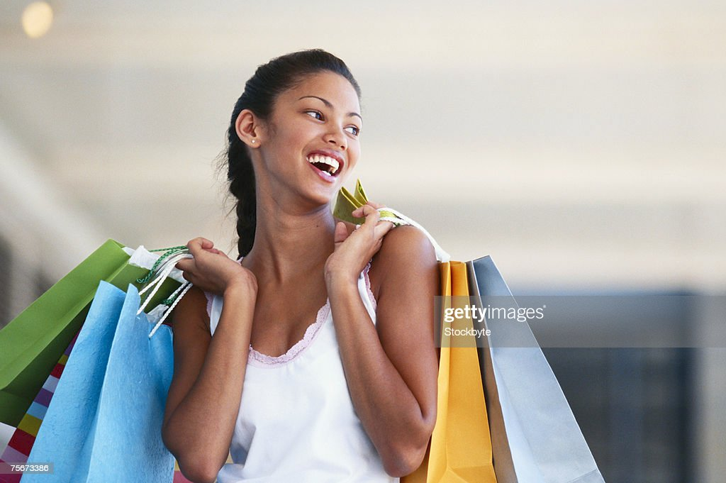 Young woman carrying shopping bags, laughing, close-up : Stock Photo