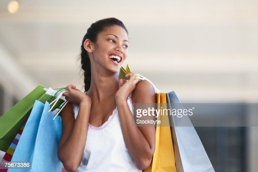Young woman carrying shopping bags, laughing, close-up : ストックフォト