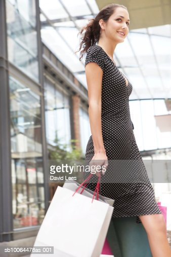 Young woman carrying shopping bags outside shop : Stock Photo