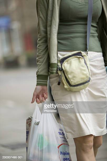 Young woman, carrying shopping, walking along sidewalk, mid section