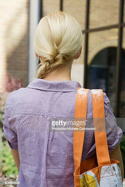 Young woman carrying shoulder bag, rear view