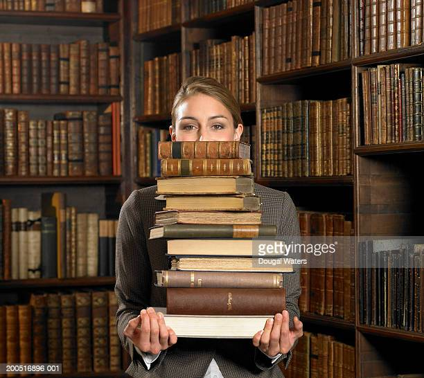 Young woman carrying stack of books in library, portrait
