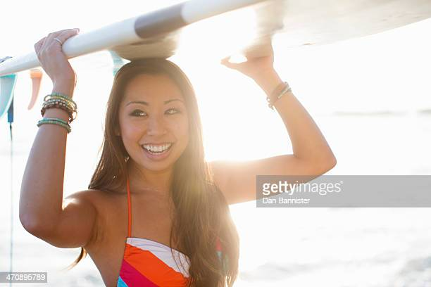 Young woman carrying surfboard, San Diego, California, USA