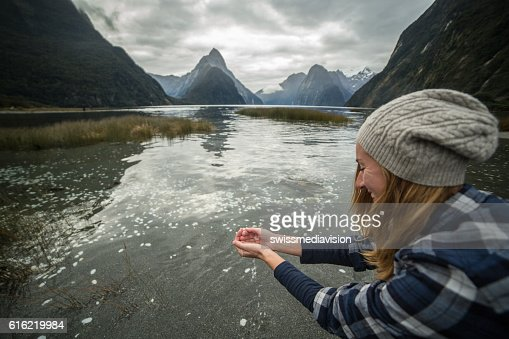 Young woman catches fresh water from lake : Stock Photo