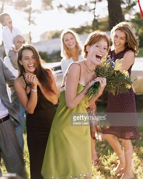 Young woman catching bouquet, smiling, portrait