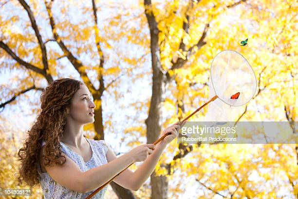 Young woman catching butterflies in Autumn forest