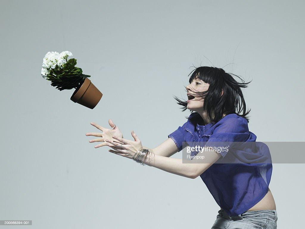Young woman catching pot plant, side view : Stock Photo