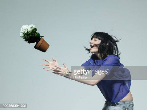 young woman catching pot plant side view stock foto getty images. Black Bedroom Furniture Sets. Home Design Ideas