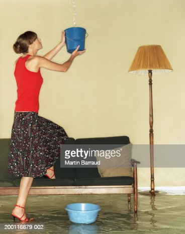 Young woman catching water in bucket in flooded room : Photo