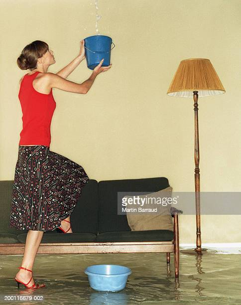 Young woman catching water in bucket in flooded room