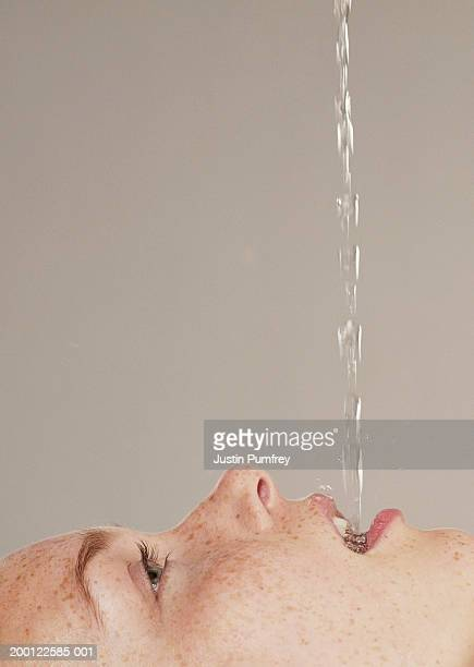 Young woman catching water in mouth, profile