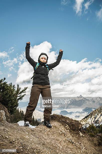 Young woman celebrating on mountain ridge, Hundsarschjoch, Vils, Bavaria, Germany