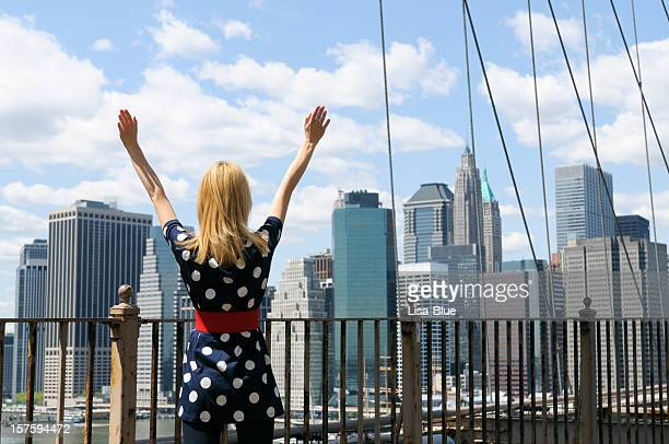 Young Woman Celebrating Success in Front of NYC Skyline