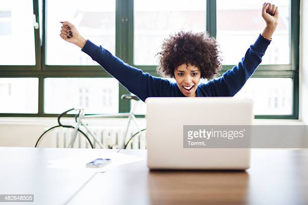 Young Woman Celebrating Success in Loft Space Behind Laptop