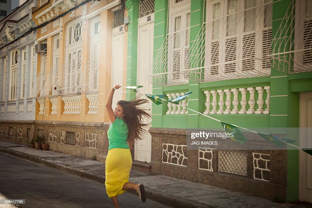 Young woman celebrating with Brazilian flags in the street, Rio de Janeiro, Brazil : Stock-Foto