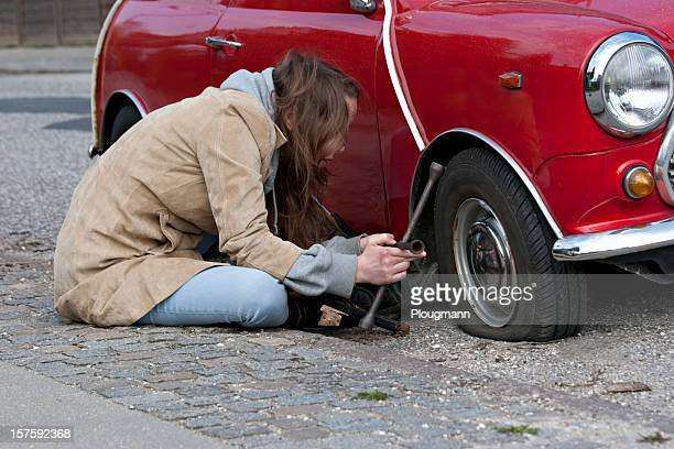 Young woman changes tire on her car