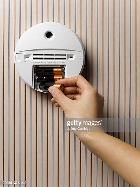 Young woman changing batteries in smoke detector