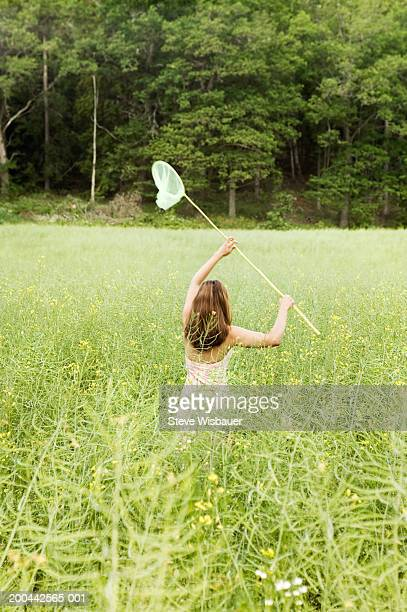 Young woman chasing butterflies in field, rear view