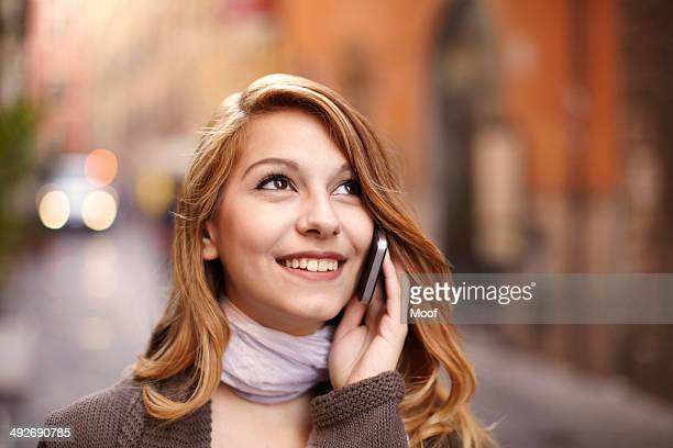 Young woman chatting on smartphone on Rome street, Italy