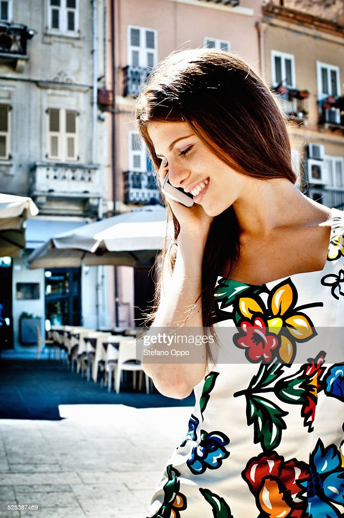 Young woman chatting on smartphone on street, Cagliari, Sardinia, Italy