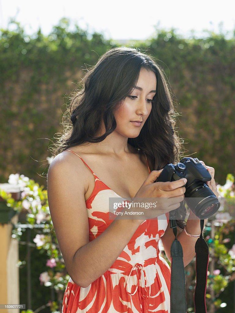 Young woman checking camera : Stock Photo