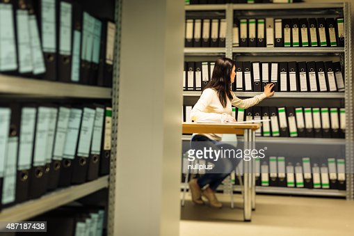 young woman checking documents in the archives