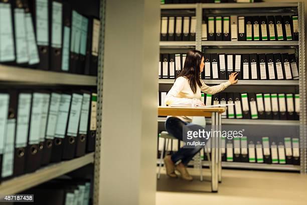 Junge Frau, die Dokumente in den Archiven